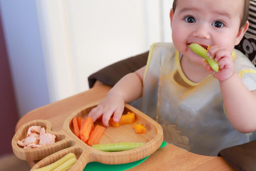 Bebé feliz comiendo salmón