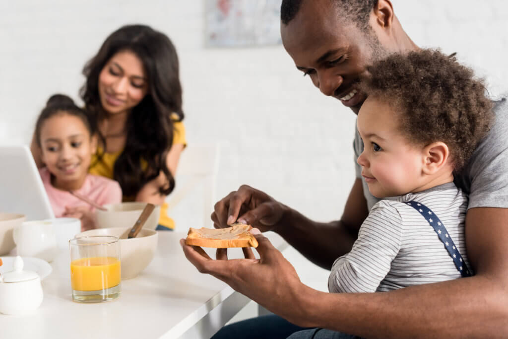Familia con bebé de 1 año desayunando fruta y tostadas