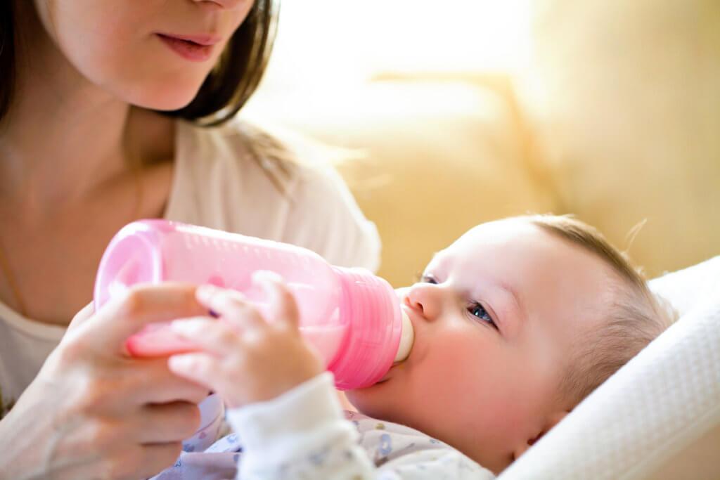 Bebé tomando un biberón de leche de fórmula